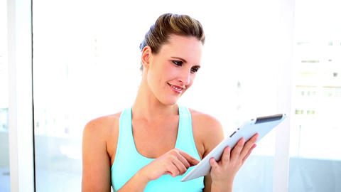 Smiling fit woman using her digital tablet Footage