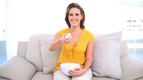 Smiling woman watching tv with popcorn on the couc Footage