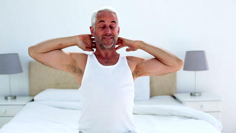 Handsome man yawning and stretching sitting on bed Live Action