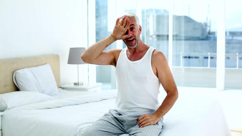 Happy man yawning and stretching sitting on bed Live Action