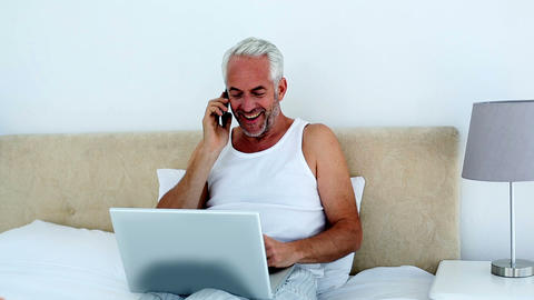 Laughing man using laptop while on the phone Footage