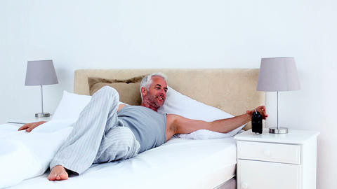 Refreshed man waking up and looking at his alarm c Footage