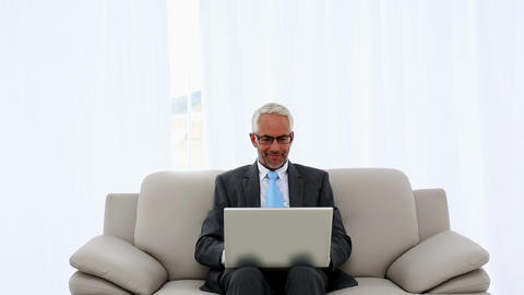 Successful businessman using laptop on the couch a Footage