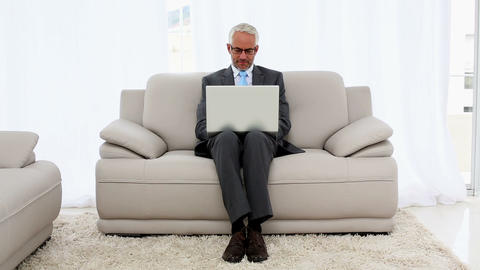Smiling businessman using laptop on the couch Footage