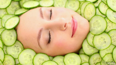Natural womans face surrounded by cucumber slices Footage
