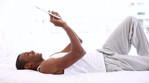 Happy man lying on bed using his tablet pc Footage