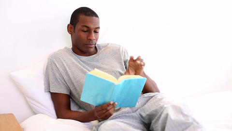 Relaxed man lying on bed reading Footage