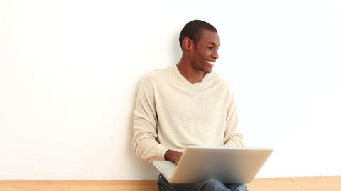 Happy man using laptop sitting on the floor Footage