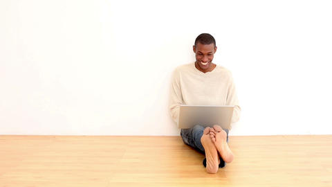 Smiling man using laptop sitting on the floor Footage