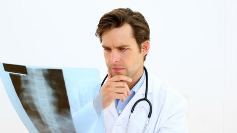 Focused doctor looking at xray Footage