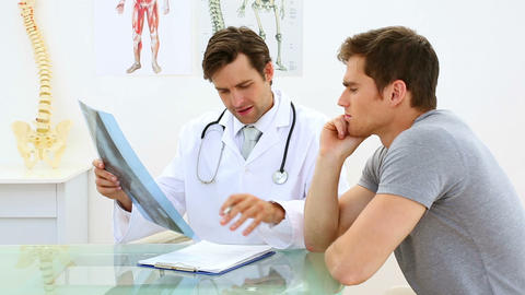 Smiling doctor discussing xray with his patient Footage