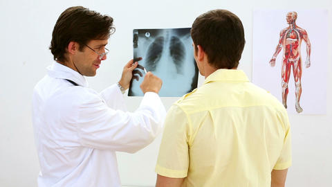 Smiling doctor looking at xray with patient Footage