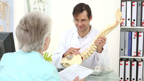 Chiropractor showing spine model to his patient Footage