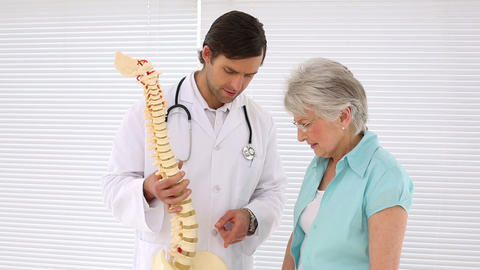 Chiropractor explaining spine model to retired pat Footage
