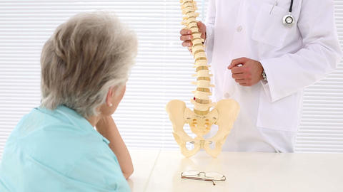 Chiropractor showing spine model to patient Footage
