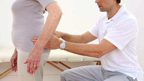 Physiotherapist touching senior patients hips Footage