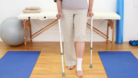 Injured patient in crutches walking towards camera Footage
