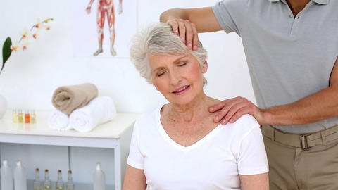 Physiotherapist stretching senior patients neck Footage