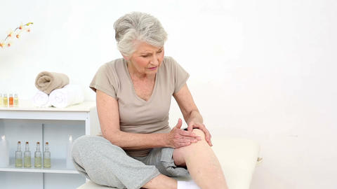 Injured patient rubbing her painful knee Footage