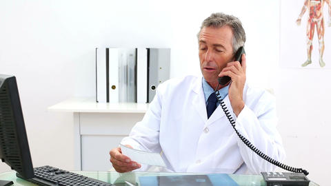 Mature doctor talking on the phone at his desk Footage