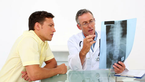 Doctor showing spine xray to his patient Footage