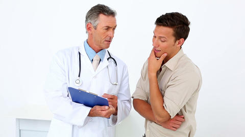 Patient talking to his doctor holding clipboard Footage