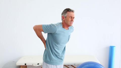 Mature patient rubbing his painful back Live Action