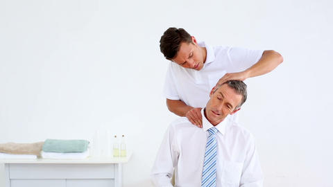 Physiotherapist giving stressed businessman a neck Live Action