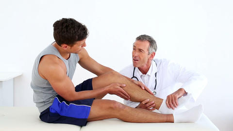 Mature doctor touching sportsmans injured ankle Footage