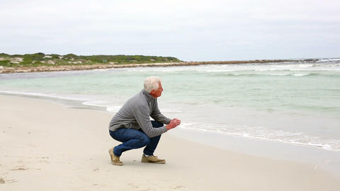 Retired man kneeling on the beach looking out to s Footage
