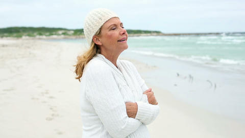 Retired woman on the beach looking out to sea Footage