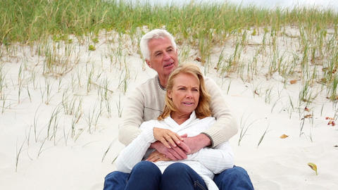 Smiling retired couple sitting on the beach Footage