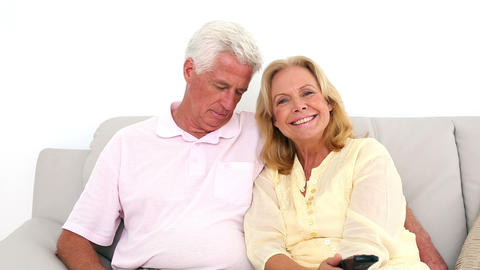 Retired couple watching television on the couch bu Footage