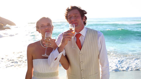 Newlyweds drinking champagne on the beach Footage