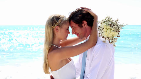 Newlyweds embracing on the beach Footage