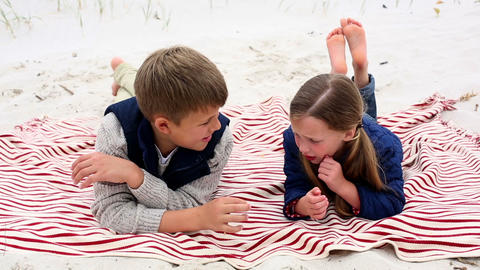 Siblings lying on blanket on the beach talking Footage