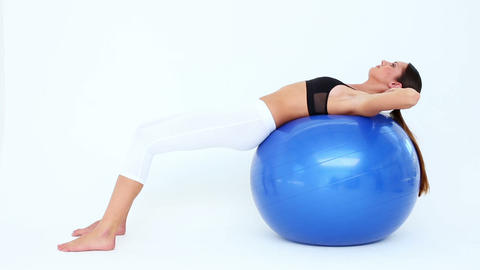 Fit woman doing sit ups on blue exercise ball Footage