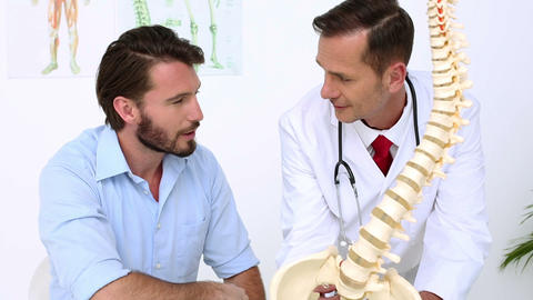 Patient Listening To Doctor Explain Spine Model stock footage