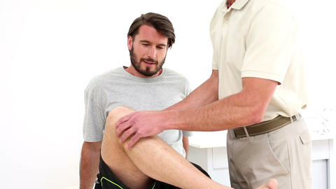 Physical therapist checking patients knee Footage