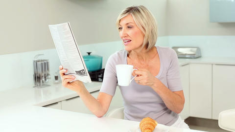 Blonde woman reading newspaper and drinking coffee Footage