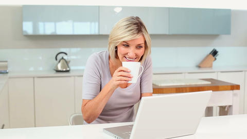Blonde woman drinking coffee while using her lapto Footage