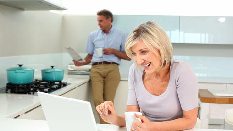 Woman using laptop while her husband is standing r Footage