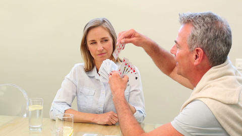 Mature couple playing cards together at the table Footage