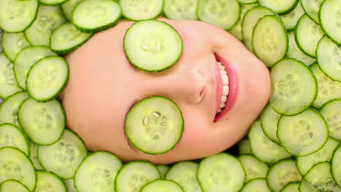 Smiling womans face surrounded by cucumber slices Footage