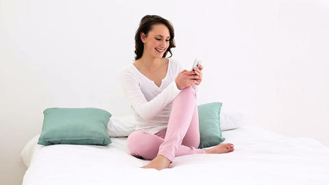 Smiling woman sitting on bed texting on the phone Footage
