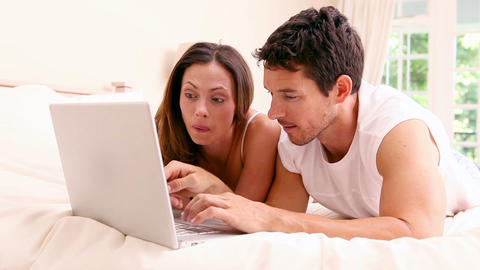 Happy couple lying on bed using laptop together Footage