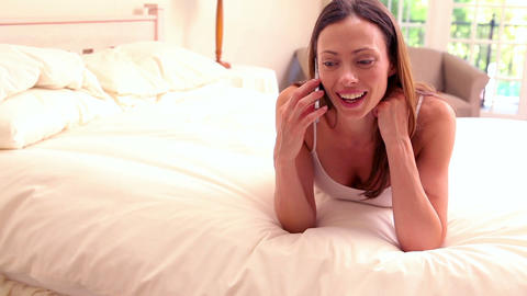 Smiling brunette lying on bed talking on her phone Footage