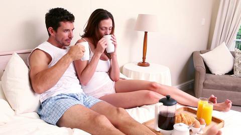 Happy couple having breakfast in bed Footage