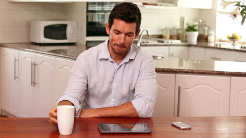 Handsome man using tablet pc at the table Footage