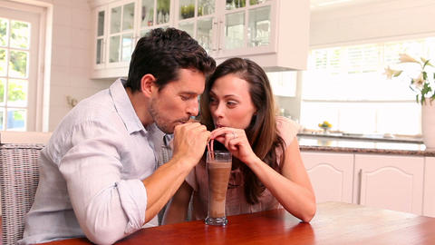 Happy couple drinking a milkshake together Footage